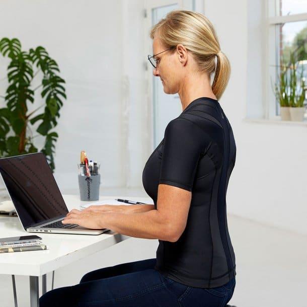Kvinde i holdningskorrigerende trøje foran en computer
